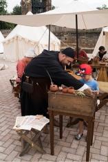 De klerk laat middeleeuws schrijven zien aan de jonge bezoekers